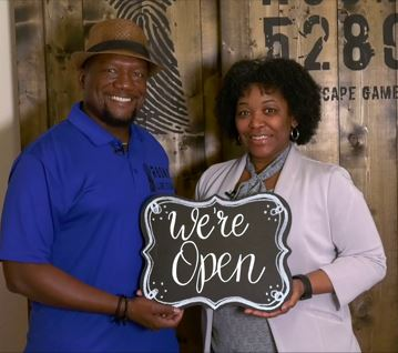 Escape Room Owners with New and Now Open Sign